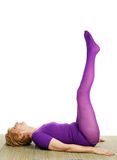 Senior Yoga - Double Leg Raise. A very fit seventy year old woman performing the double leg raise position in yoga. White background Stock Photos