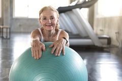 Senior at yoga gym posing leaning on her ball smiling and happy. elderly healthy lifestyle.  royalty free stock photography