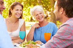 A senior and a young adult couple eating together outdoors Stock Images