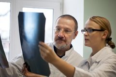 Senior and young doctors examining x-ray images Royalty Free Stock Image