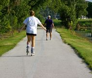Senior and Young Exercising Together. Senior man and Young lady exercising in the park. Photographed at Largo Central Park, Largo Florida Royalty Free Stock Photography