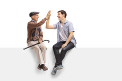 Senior and young guy on a panel high-fiving each other Stock Photography