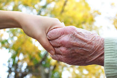 Senior and young holding hands Stock Photos