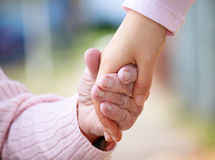 Senior and young holding hands Stock Image
