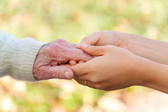 Senior and young holding hands Royalty Free Stock Photography
