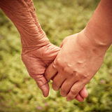 Senior and young holding hands Royalty Free Stock Images