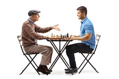 Senior and a young man playing chess. Senior and a young men playing chess isolated on white background royalty free stock photos
