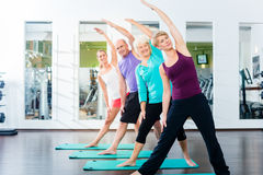 Senior and young people doing gymnastics in gym Royalty Free Stock Photography