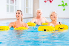 Senior and young people in water gymnastics. With resistance device Stock Image