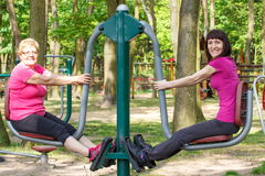 Senior and young woman exercising lower body on outdoor gym, healthy lifestyle Royalty Free Stock Photos