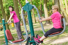 Senior and young woman exercising lower body on outdoor gym, healthy lifestyle Royalty Free Stock Image