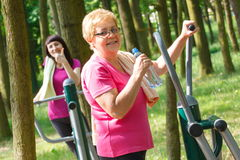Senior and young woman exercising upper body on outdoor gym, healthy lifestyle Royalty Free Stock Image