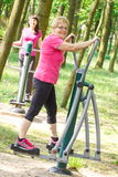 Senior and young woman exercising upper and lower body on outdoor gym, healthy lifestyle Stock Photography