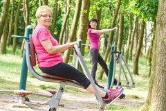 Senior and young woman exercising upper and lower body on outdoor gym, healthy lifestyle Royalty Free Stock Photo