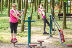 Senior and young woman exercising upper and lower body on outdoor gym, healthy lifestyle Royalty Free Stock Photography