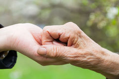 Senior & young woman holding hands Stock Photo