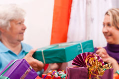 Senior and young women give presents to each other Stock Photos