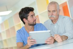 Senior and young working together on project in office Stock Photography