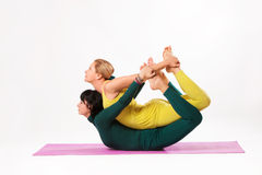 Senior and younger woman practice yoga. Senior women and younger women practice yoga, bow pose, studio shot stock photo