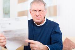 Senior zu Hause, der negative Mitteilung empfängt Lizenzfreie Stockfotografie
