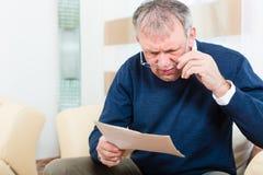 Senior zu Hause, der negative Mitteilung empfängt Lizenzfreie Stockfotos