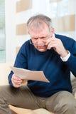 Senior zu Hause, der negative Mitteilung empfängt Lizenzfreie Stockbilder