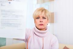 Senior zu Hause, der negativen Brief erhält Lizenzfreies Stockfoto