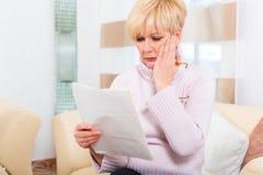 Senior zu Hause, der negativen Brief erhält Stockfotos