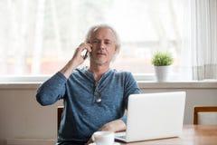 Seniora dojrzały mężczyzna opowiada na telefonie robi wezwaniu w domu obrazy royalty free