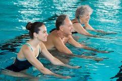 Senioren, die auf Aquafahrrad radfahren lizenzfreies stockbild
