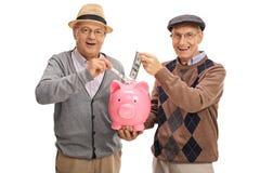 Senioren, die Geld in ein piggybank einsetzen und die Kamera betrachten Stockbilder