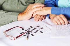 Senioren, die Hände in der Krankenpflege anhalten Stockfotos