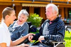 Senioren, die Süßigkeit im Garten des Pflegeheims essen Stockbilder