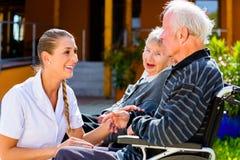 Senioren, die Süßigkeit im Garten des Pflegeheims essen Lizenzfreies Stockbild