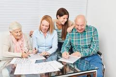 Senioren lösen Puzzlespiele als Dressur Lizenzfreie Stockfotos