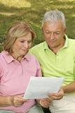 Senioren lasen Papier Stockfoto