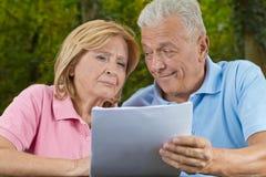 Senioren lesen und lächeln Stockfotos