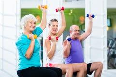 Senioren mit Trainer in der Turnhalle an Sport anhebendem Barbell Lizenzfreie Stockfotografie