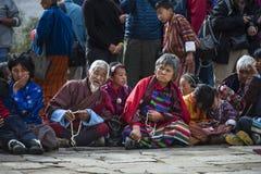 Senioren von Bhutan kleiden herkömmlich an und halten Gebetsperlen bei Puja, Bumthang, Mittel-Bhutan stockbild
