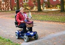 Seniorin med den elektriska sparkcykeln Royaltyfri Fotografi
