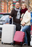 Seniorpleasant couple of travellers posing with trollers Royalty Free Stock Images