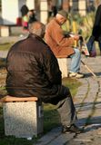 Seniors. Image of two elderly men siting on benches focus is on the man in the front ground and shallow DOF Royalty Free Stock Photos