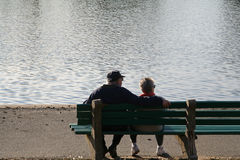 Seniors. Old timers sitting on a bench relaxing near water royalty free stock image