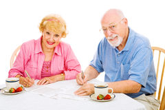 Seniors with Absentee Ballots. Senior couple filling out their absentee ballots for upcoming election. Isolated on white stock images