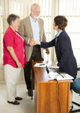 Seniors Apply for Loan. Senior couple meet loan officer to fill out application stock photos
