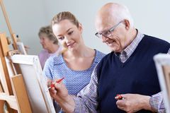 Seniors Attending Painting Class With Teacher. Senior Man Attending Painting Class With Teacher Stock Images