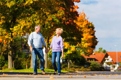 Seniors in autumn or fall walking hand in hand Royalty Free Stock Image
