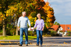 Seniors in autumn or fall walking hand in hand Stock Photos