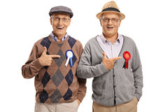 Seniors with award ribbons pointing Royalty Free Stock Images