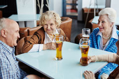 Seniors with beer. Group of friendly seniors having beer in cafe Stock Images